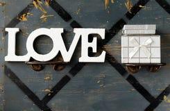 las letras aman y la caja de regalo, el día de tarjeta del día de San Valentín Imágenes de archivo libres de regalías