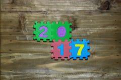 Las letras de molde y numeran 2017 con el fondo de madera Imagenes de archivo