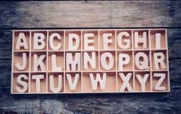 Las letras inglesas se ponen en una caja de madera en orden alfabético foto de archivo libre de regalías
