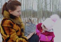 Las liebres del conejo al aire libre nievan niño lindo poca familia sonriente ch del invierno del bebé del invierno de la mujer d Fotos de archivo