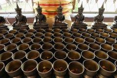 Las limosnas de la estatua y del monje del ángel ruedan con pusieron las monedas Foto de archivo libre de regalías