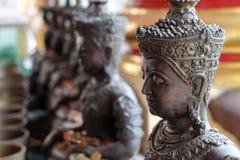 Las limosnas de la estatua y del monje del ángel ruedan con pusieron las monedas Fotos de archivo