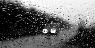 Las linternas de los coches inminentes en tiempo lluvioso Foto de archivo libre de regalías