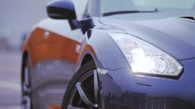 Las linternas del nuevo coche azul marino se colocan en el estacionamiento Presentación del automóvil Sombras frías almacen de metraje de vídeo