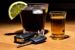 Las llaves del coche pusieron en la barra al lado del cóctel y del whisky Imágenes de archivo libres de regalías