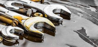 Las llaves, nueces - y - los pernos mancharon con aceite de motor Fotografía de archivo libre de regalías
