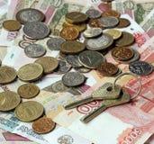 Las llaves y el dinero ruso en la tabla de madera Rublos y copecs Fotografía de archivo