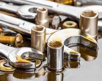 Las llaves y las herramientas del mecánico mancharon con aceite de motor Imagen de archivo