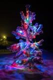 Las luces brillantes de un árbol de navidad natural cubrieron nieve. Imagen de archivo