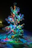 Las luces brillantes de un árbol de navidad natural cubrieron nieve. Fotografía de archivo