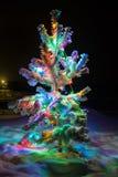 Las luces brillantes de un árbol de navidad natural cubrieron nieve Imagenes de archivo