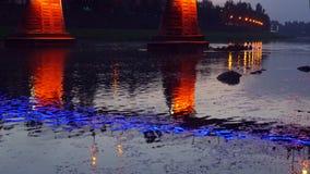 Las luces brillantes en puente de la ciudad de la noche reflejaron en las luces Uzgorod del río almacen de video