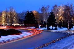 Las luces de coches en el camino en invierno Imagen de archivo