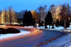 Las luces de coches en el camino en invierno Imágenes de archivo libres de regalías