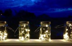 Las luces de hadas dentro del tornillo retro del vintage rematan los tarros con las manijas Fotografía de archivo