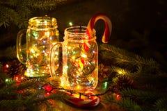 Las luces de hadas de la guirnalda de la Navidad en un tarro de cristal brillan en la oscuridad de la noche Foto de archivo libre de regalías