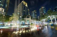 Las luces de la característica del agua del puerto deportivo de Dubai se encendieron para arriba en la noche con las señales famo Imagenes de archivo