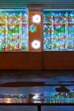 Las luces de la Navidad, el banco mojado y la lluvia pudelan Foto de archivo libre de regalías