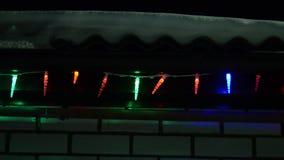 Las luces de la Navidad multicoloras adornan la casa en la noche, guirnalda brillante en el tejado del invierno, mentiras de la n almacen de metraje de vídeo