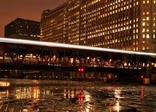 Las luces de la noche de la ciudad están iluminadas del puente de Chicago y del tren de mudanza del EL que apresuran a través de  Fotografía de archivo