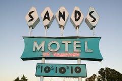 Las luces de neón se adelantan en la puesta del sol en el motel de las arenas con el estacionamiento de rv para $10, situado en l Imagenes de archivo