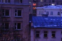 Las luces de las ventanas de las casas de la tarde Imagen de archivo
