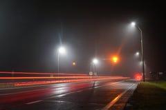 Las luces del camino iluminan la pista vacía foto de archivo