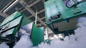 Las máquinas de la fábrica funcionan con la fibra de poliéster blanca en un transportador almacen de metraje de vídeo