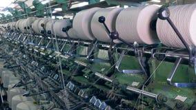 Las máquinas de la fábrica de la materia textil funcionan con las bobinas de giro en filas Fábrica industrial de la materia texti almacen de metraje de vídeo