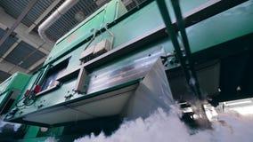 Las máquinas modernas funcionan en una fábrica no tejida de la tela, materiales móviles metrajes