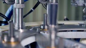 Las máquinas neumáticas llenan las botellas de leche en la visión cercana metrajes