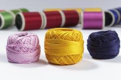 Las madejas del algodón roscan en primero plano con las bobinas para las máquinas de coser en el fondo Imagen de archivo