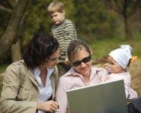 Las madres están utilizando una computadora portátil Fotografía de archivo