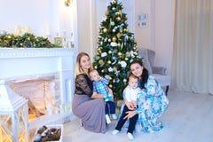 Las madres jovenes presentan y sonriendo con sus pequeños niños cerca de w Imagen de archivo libre de regalías