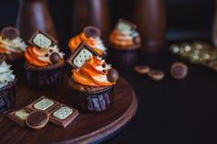Las magdalenas con crema en un vidrio oscuro, adornado con el chocolate, las galletas se colocan en un soporte de la madera oscur Imagen de archivo