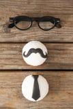 Las magdalenas con el bigote y el lazo forman el decorataion por las lentes en la tabla Imágenes de archivo libres de regalías