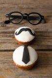 Las magdalenas con el bigote y la corbata forman el decorataion por las lentes en la tabla Fotos de archivo libres de regalías