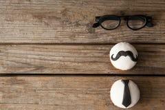 Las magdalenas con el bigote y la corbata forman el decorataion por las lentes en la tabla de madera Fotos de archivo libres de regalías