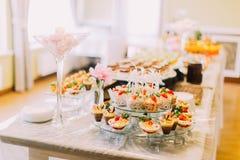 Las magdalenas deliciosas de la boda están poniendo en el soporte del postre mientras que las melcochas rosadas en el florero eno Fotografía de archivo