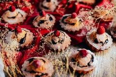 Las magdalenas deliciosas del chocolate con las bayas encendido wodeen la tabla, v superior Imagen de archivo libre de regalías