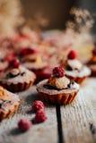 Las magdalenas deliciosas del chocolate con las bayas encendido wodeen la tabla, v superior Fotos de archivo
