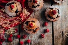 Las magdalenas deliciosas del chocolate con las bayas encendido wodeen la tabla, v superior Imagen de archivo