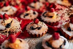 Las magdalenas deliciosas del chocolate con las bayas encendido wodeen la tabla, v superior Imágenes de archivo libres de regalías