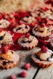 Las magdalenas deliciosas del chocolate con las bayas encendido wodeen la tabla, v superior Imagenes de archivo