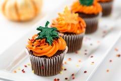 Las magdalenas deliciosas del otoño adornadas con helar anaranjado, colorido asperjan y las hojas de arce Foto de archivo libre de regalías