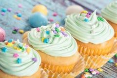 Las magdalenas en colores pastel de Pascua con el caramelo y asperjan Foto de archivo