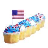Las magdalenas patrióticas adornadas con la bandera americana y la crema azul, blanca con las estrellas rojas asperjan en el top,  Foto de archivo