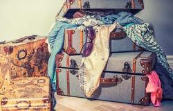 Las maletas viejas del vintage abarrotaron con ropa y gafas de sol Foto de archivo libre de regalías