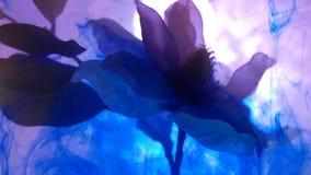 Las manchas abstractas del color de la tinta en el agua envuelven la flor almacen de metraje de vídeo