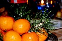 Las mandarinas maduras anaranjadas están en la tabla Preparación de la tabla para la celebración del Año Nuevo imagen de archivo